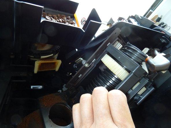 Nun ist die Brühgruppe frei. Kippe sie unten heraus, achte dabei auf den Druckschlauch. Er muss durch eine Öffnung hindurchgeführt werden. Drücke dann die Brühgruppe ein wenig nach unten und hebe sie aus dem Gerät heraus.