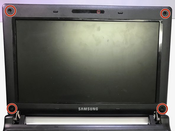 Remove the four black screw covers located at all corners of the screen with tweezers to expose the screws