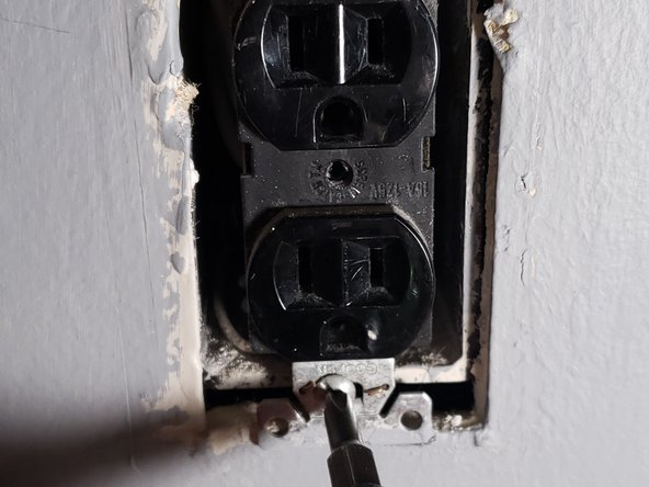Unscrew the top and bottom screws holding the outlet into the interior electrical box.