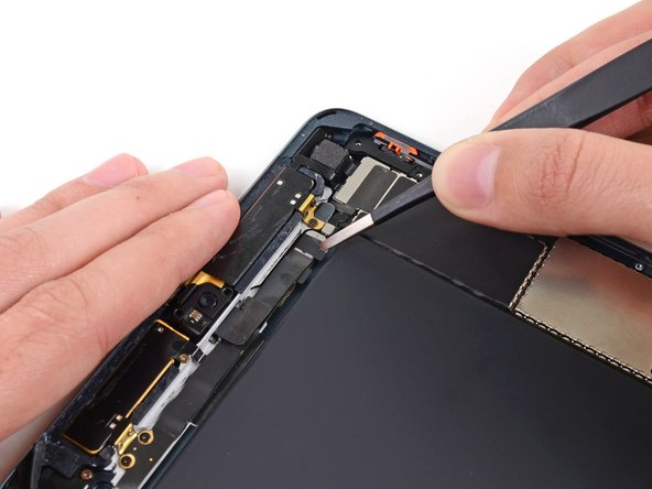 Use a pair of tweezers to peel up and remove the small piece of tape covering the front-facing camera cable connector.