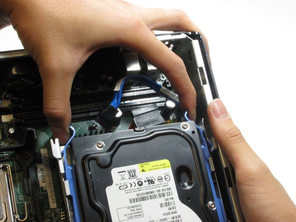 Squeeze the release tabs on either side of the hard drive.
