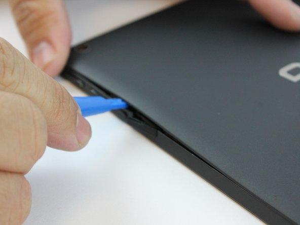 En commençant par l'emplacement de carte Micro SD et en utilisant l'outil d'ouverture en plastique bleu, commencez à manœuvrer l'outil autour des bords tout en appliquant une légère pression pour soulever le panneau vers le haut.