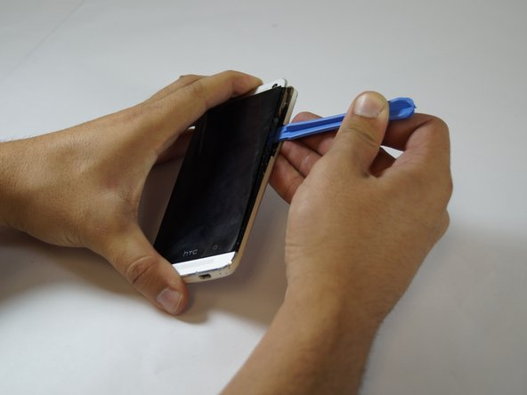 In this step you'll lift the screen. Be VERY gentle else you will break it. Insert the plastic opening tool in between the black plastic bezel and the glass screen edge along the sides and the top, gently loosening the adhesive. The screen will remain attached at the bottom edge, as if on a hinge.