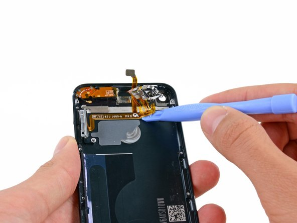 Slide a plastic opening tool from right to left underneath the horizontal section of the cable, separating it from the adhesive securing it to the rear case.
