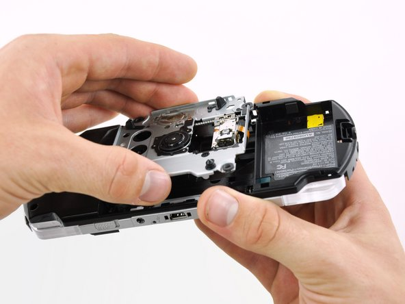 Lift the UMD drive out of the PSP 300xc, minding any cables that may get caught.