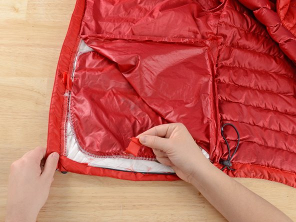 If your jacket has a pocket, make sure the two tabs holding the pocket in place are free.