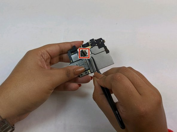 Using the angled tweezers, disconnect the rear camera from the motherboard.