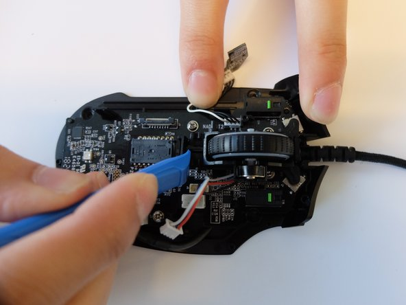 Using the opening tool, pry the black bracket holding the scroll wheel in place backwards until the scroll wheel housing pops out.