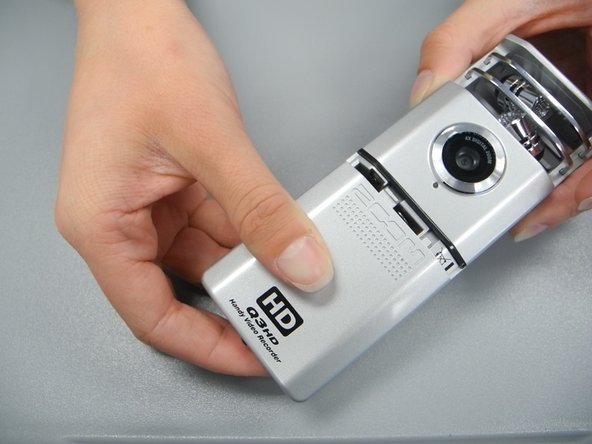 On the front of the device, slide the battery compartment cover off by pushing inward and sliding downward.