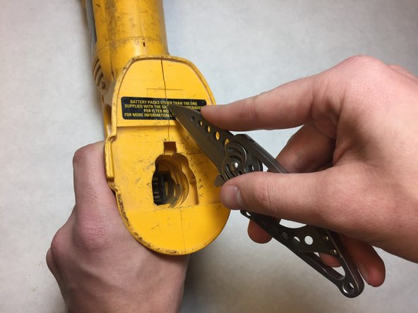 Carefully cut the safety sticker with a blade along the seam.