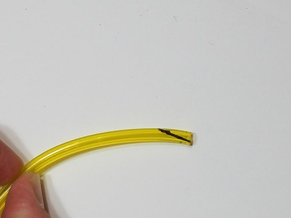 Cut a piece of the thicker diameter fuel line at a sharp angle