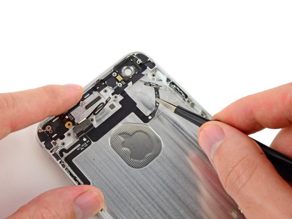 Pull the power button switch out of its recess on the rear case with a pair of tweezers, and begin carefully peeling the power button cable from the rear case.
