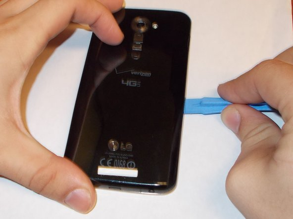 Using the plastic opening tool, or the thin side of the spudger to separate the back cover from the phone. Start at the bottom corner of the phone. Be gentle because it may cause cosmetic and internal damage if not done with care.