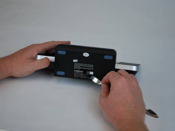 Begin by using a metal spudger to peel back the adhesive sticker and locate the 11mm screw beneath the sticker.