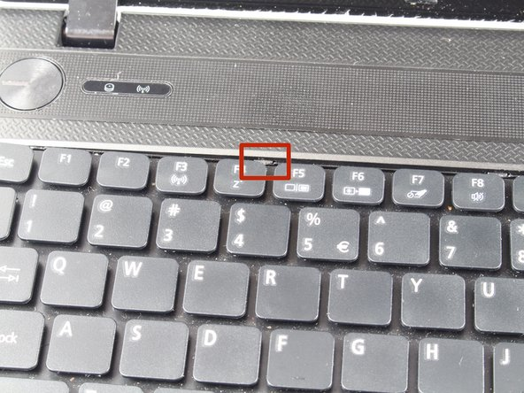 Locate the tabs keeping the keyboard in place.