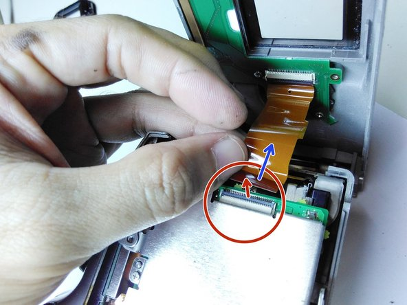 Locate the connector which holds the flat cable to the main circuit board. Unlock the connector by gently pulling  up its black piece from the side the flat cable comes into it.