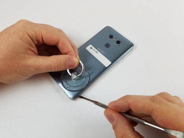 When the back panel is heated, apply the suction cup close to a corner of the phone.  Lift up and insert a halberd spudger or opening pick under the rear glass.