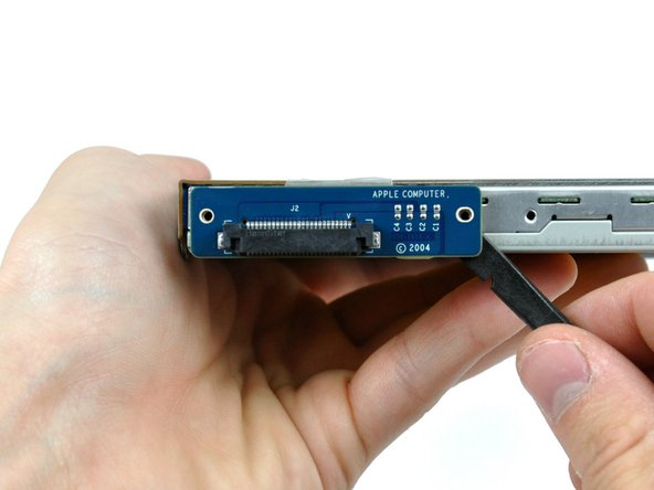 Working from alternating sides of the board, use the flat end of a spudger to separate the optical drive connector board from the optical drive.