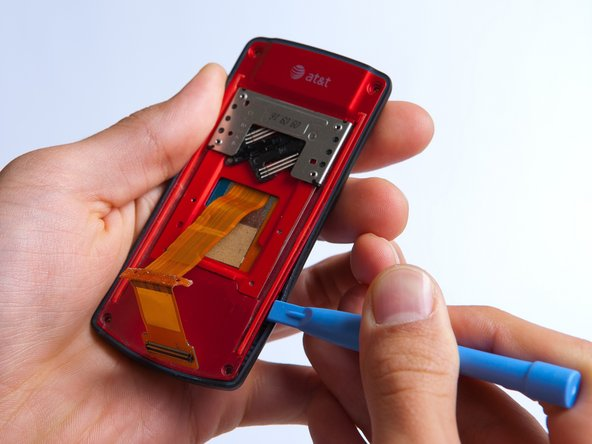 Pry the red sliding backing from the front cover by inserting the plastic opening tool in between the two sections and going around the entire phone.