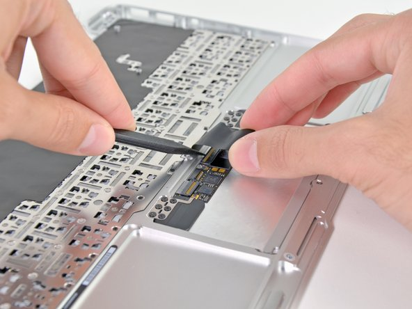 With one hand, lift the keyboard ribbon cable up and push it slightly away from the trackpad to access the ZIF connector underneath.