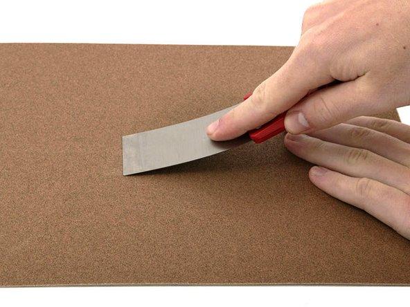 Vous aurez besoin d'un couteau à mastic pour ouvrir le boîtier. Un couteau mince de 4 cm fonctionnera bien, mais vous devriez en poncer le bord. Frottez le bord court du couteau à mastic d'avant en arrière sur une feuille de papier de verre à grain grossier (100 grains fonctionnent bien) jusqu'à ce que le bord soit biseauté.