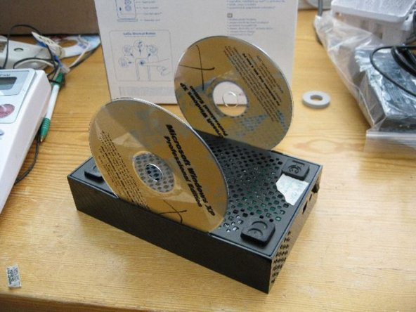 Use a thin plastic or metal thing (like a putty knife) to pry the plastic away from the metal bottom on one of the long sides. Insert a CD or a credit card that you don't care about into the gap to hold it open.