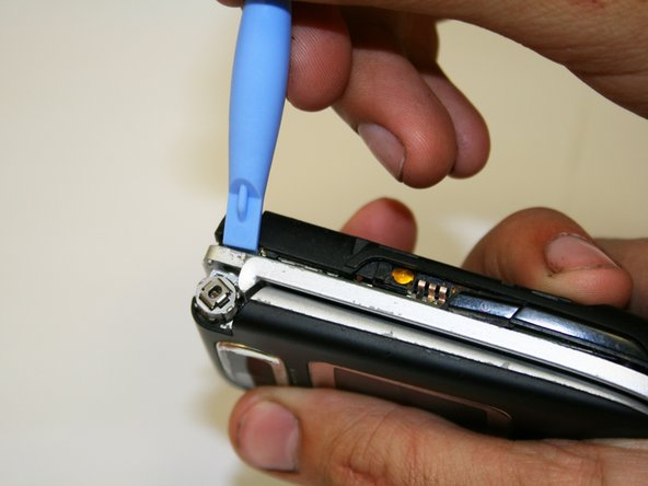 Use an iPod opening tool to gently pry open the back case as indicated in the picture.