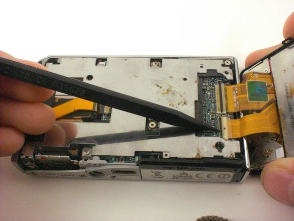 Lift the back cover, being careful not to rip the orange cables between the camera and the back cover.