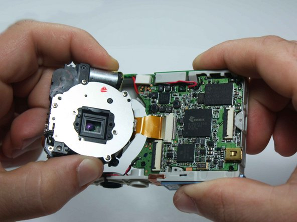 Carefully unplug the golden wire from the motherboard to remove the lens from the assembly.
