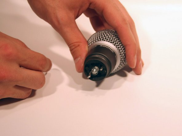 Using an adjustable wrench, remove the nut and the washer behind the face plate by twisting the nut counterclockwise.