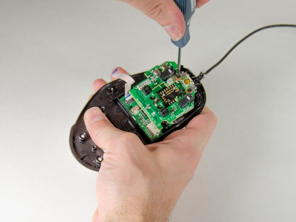 Remove the final two Phillips screws near the top of the mouse holding the circuit boards to the plate.