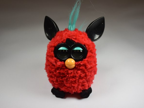 Use a flathead screwdriver to remove the two 10mm screws on the base of the Furby.