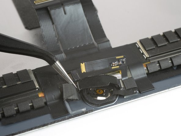 Lift the home button bracket starting from the left side.