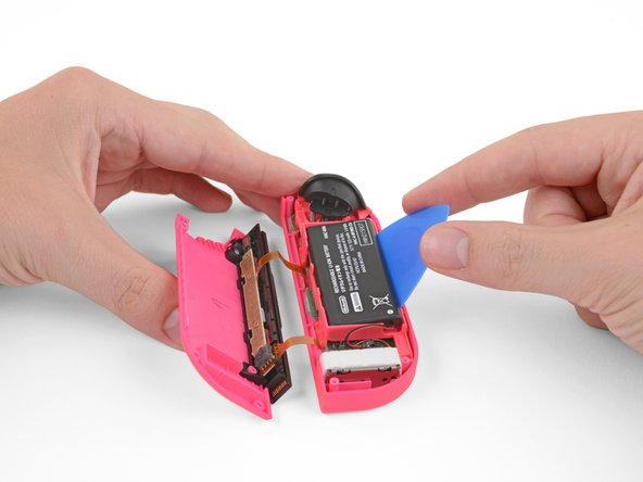 Insert an opening pick between the battery and the Joy-Con housing.