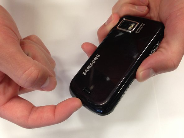 Slide your fingernail into the slit at the bottom of the phone to remove the back cover.