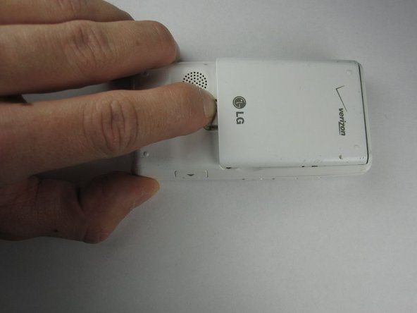 Find a sliding button on the lower back side of the device and with your finger, slide it to the left firmly.
