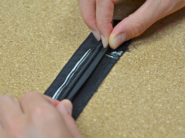 Take the side of the zipper that had the webbing, and lay it back into the webbing, aligning the zipper tape edge along the serged edge of the webbing.