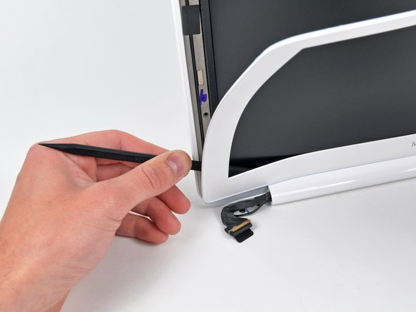 Slowly work your way across the lower edge of the front display bezel until it is free from the display assembly.