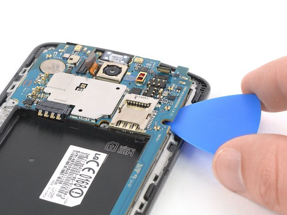 Slide the opening pick under the right edge of the motherboard where the SIM card slot is located and pry it up by rotating the opening pick sideways.