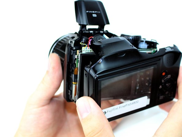 Gently, remove the rear case from the camera and set it aside.