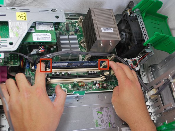 Using your index fingers, press the two tabs on the sides of the RAM stick.