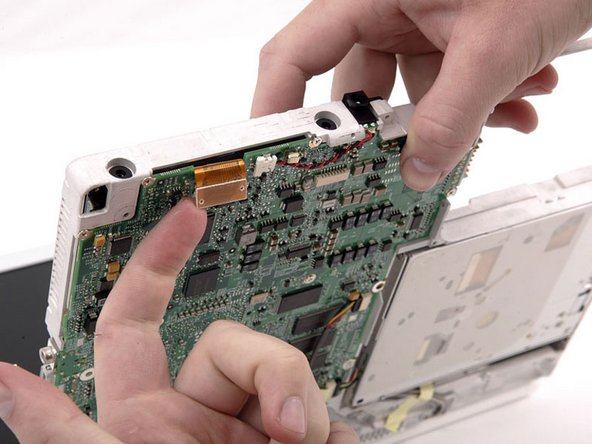 Hold the hard drive in place with one hand while tilting the computer up.
