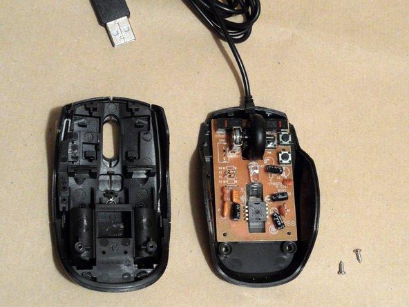 Soulevez le couvercle où se trouvaient les vis et déplacez-le légèrement vers l'arrière (loin du câble). Tout le reste à l'intérieur de la souris se détache avec cette étape.
