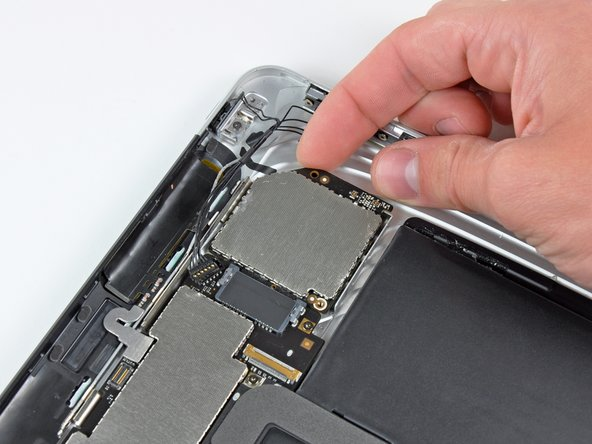 If necessary, lift the right edge of the communications board upward to release it from the adhesive pad attached to the rear case.