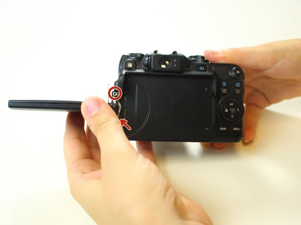 Flip the LCD screen perpendicular to the camera exposing the side screws.