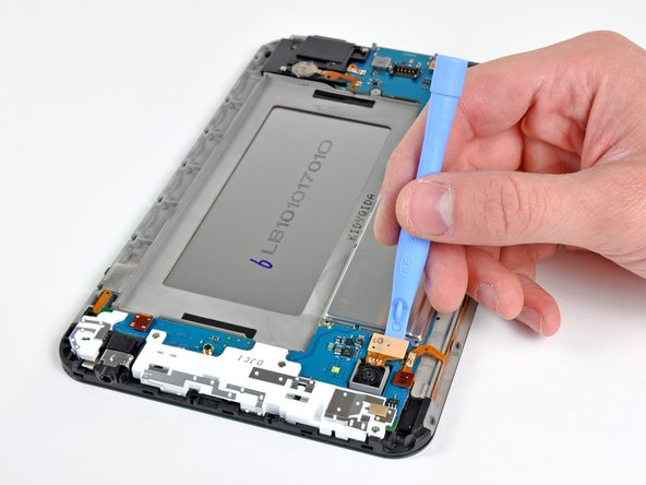 The rear-facing camera connector is pried up from its socket on the motherboard with the edge of an opening tool.