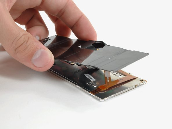 Lift the back cover off the display assembly, feeding the ribbon cable through the slit as you go.