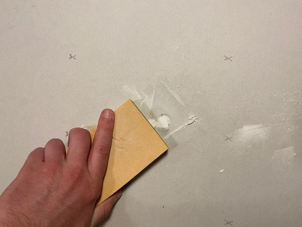 Press the sandpaper against the wall and scrub on and around the hole, to level it with the wall.