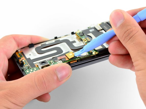 Next, we use a plastic opening tool to lift the camera ribbon cable off its socket on the motherboard.