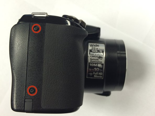 On the left side of the camera, use a Phillips #00 Precision Screwdriver to remove the two marked screws.